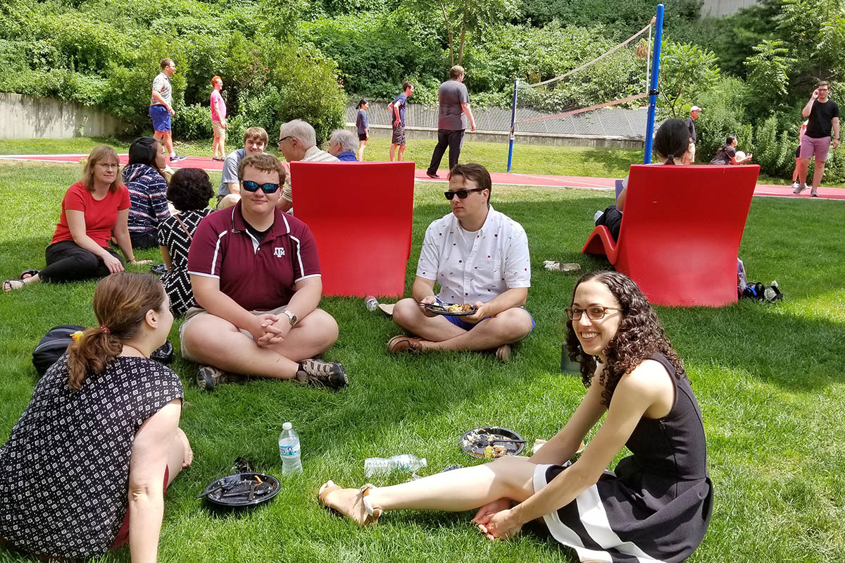 some students sitting on ground eating lunch, some playing volleyball at summer picnic