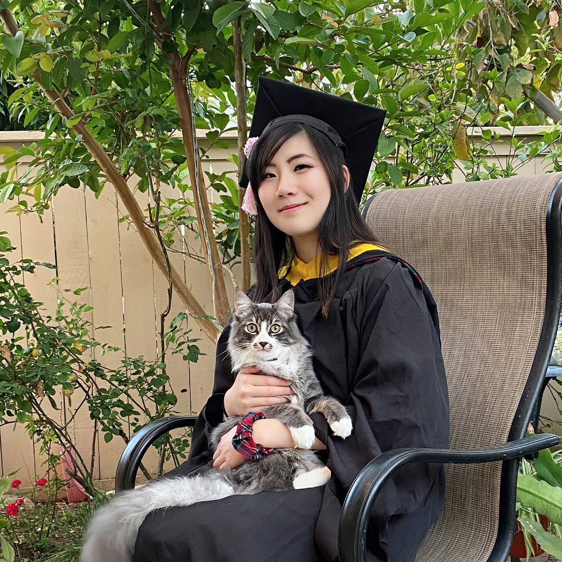 Connie is wearing her black CMU cap and gown. She is sitting outdoors in a chair and holding her cat.