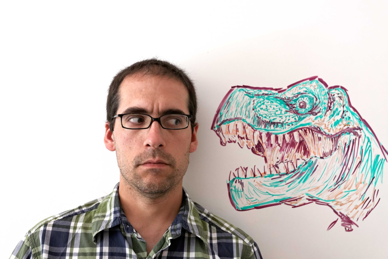 Derek Wahila looks out of the corner of his eye at a dinosaur drawn beside him on a whiteboard
