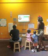 2 adults and 2 children play with the Norilla system in a museum