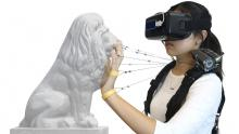 student wearing VR headset on face touches the face of a lion statue while wires connect fingers to the Wireality device on her shoulder