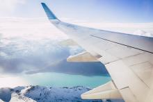 looking of the left side of a plane in flight, view of the left wing flying over snowcapped mountains