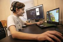 young student smiles while sitting at desk with laptop and extra screen and playing a game online