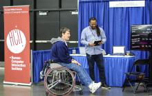 Patrick Carrington speaks with an athlete at the NWBT about SpokeSense