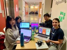 four student team members sit around a table during the hackathon and show their laptop screens while working on Lucid Drums